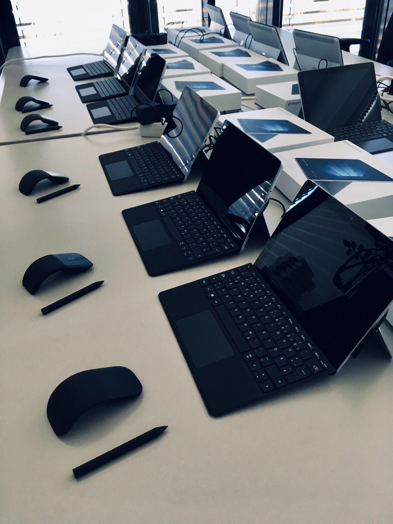 Elf Surface Go Devices inklusive Tastauren, Mäusen und Classroom Pen sind in einer Reihe auf Tischen platziert
