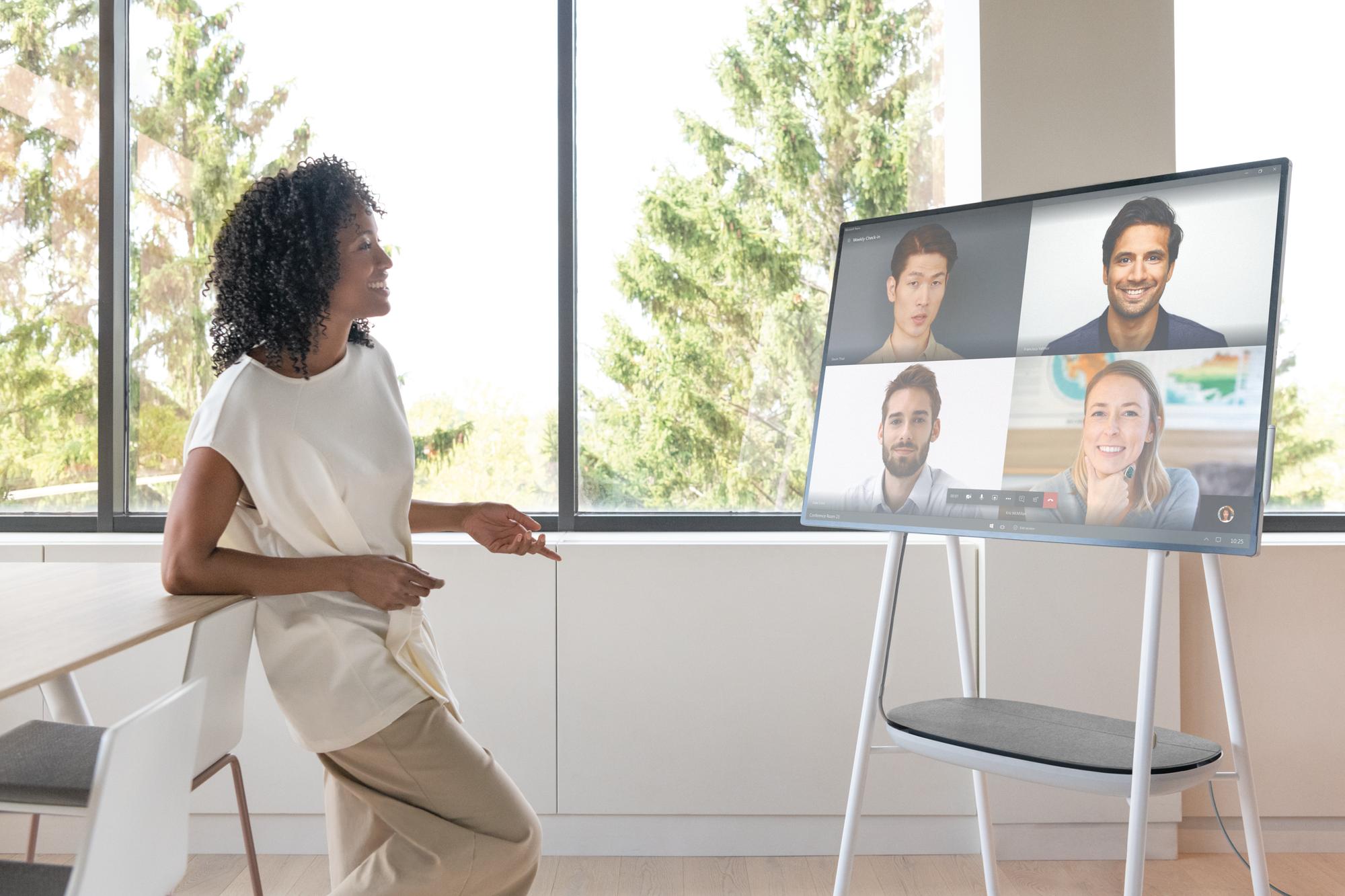 Eine Frau spricht mit 4 Personen über das Surface Hub in der geöffneten Microsoft Teams App in einem Video-Chat
