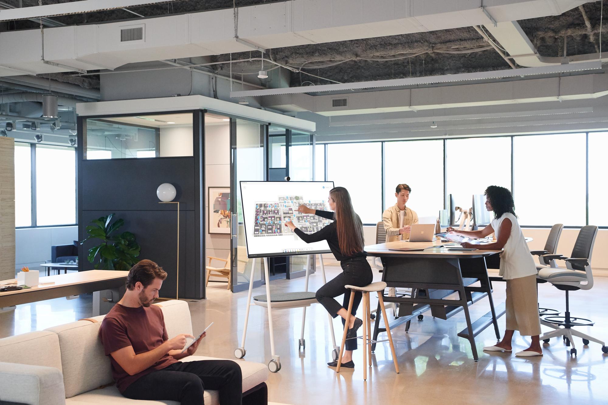 In einem Büro arbeiten mehrere Personen an ihren Surface Devices, eine Frau arbeitet am Surface Hub 2S