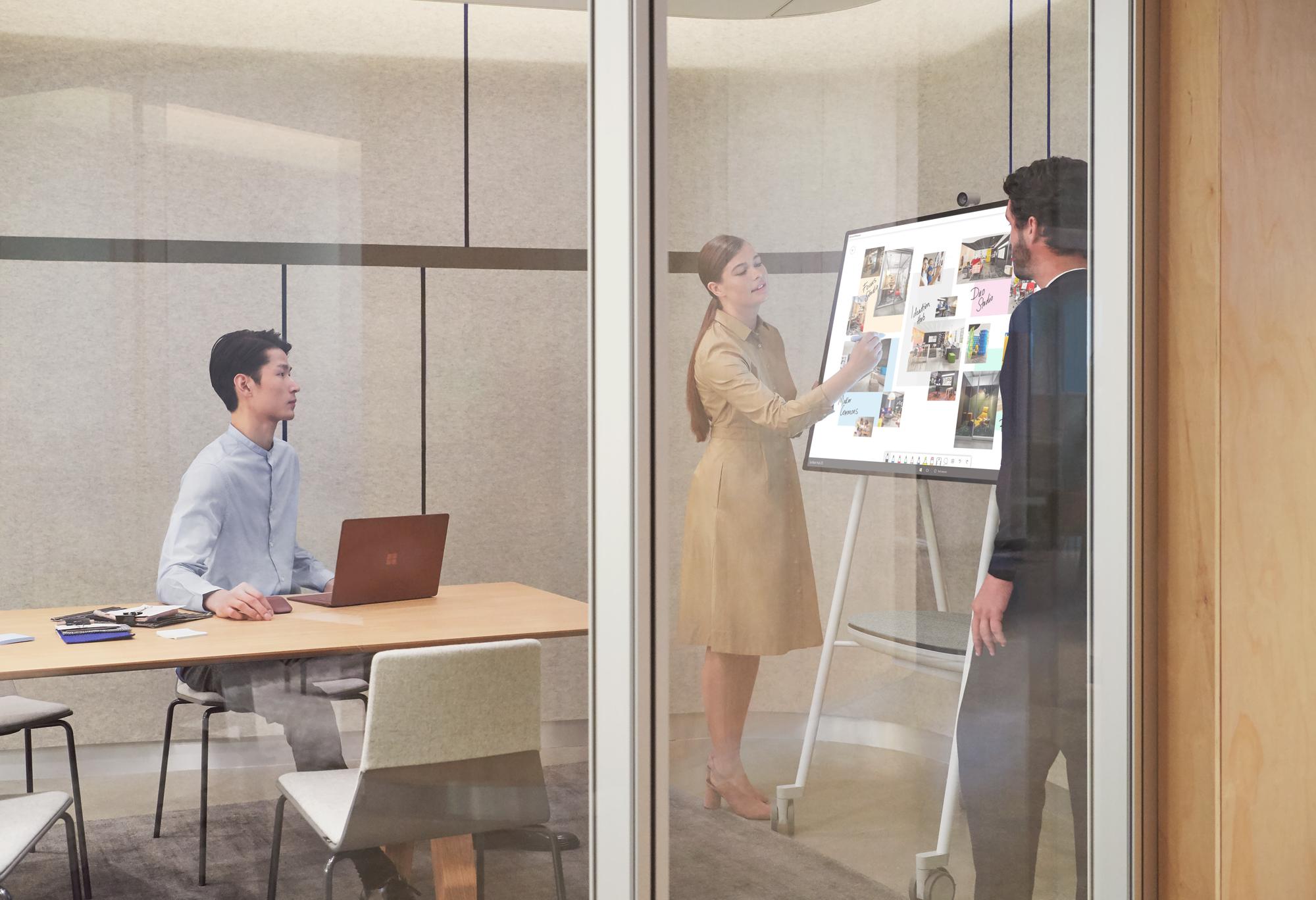 In einem Büroraum sitzt ein Mann am Tisch mit dem Surface Laptop und schaut auf ein Surface Hub, auf dem eine Frau etwas mit dem Surface Hub 2 Pen tippt, ein weiterer Mann betritt ebenfalls den Raum
