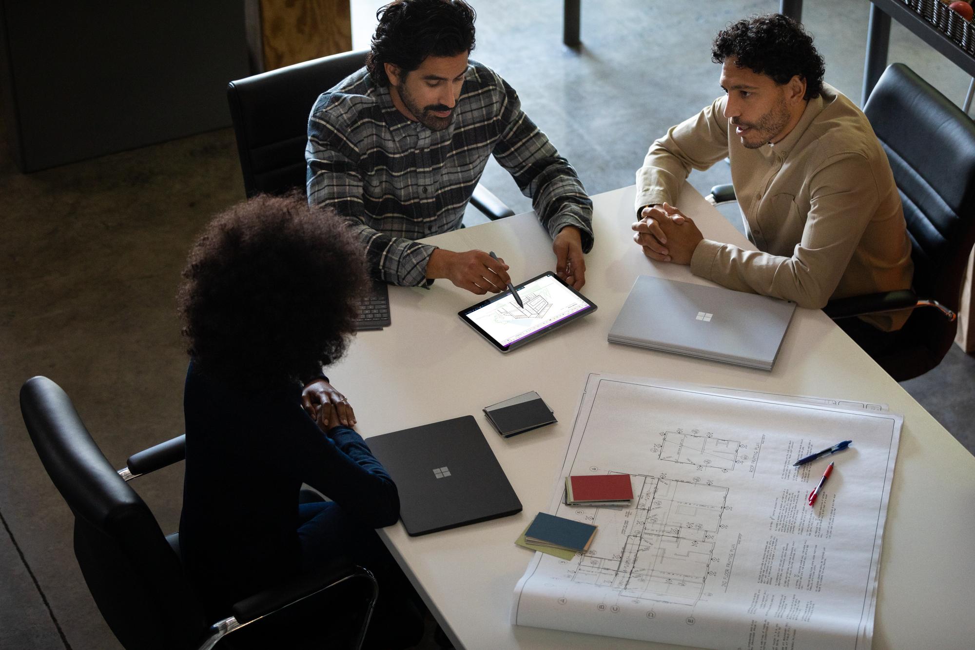 Kollegen sitzen an einem Tisch und arbeiten am Surface Go 2 eine digitale Zeichnung aus