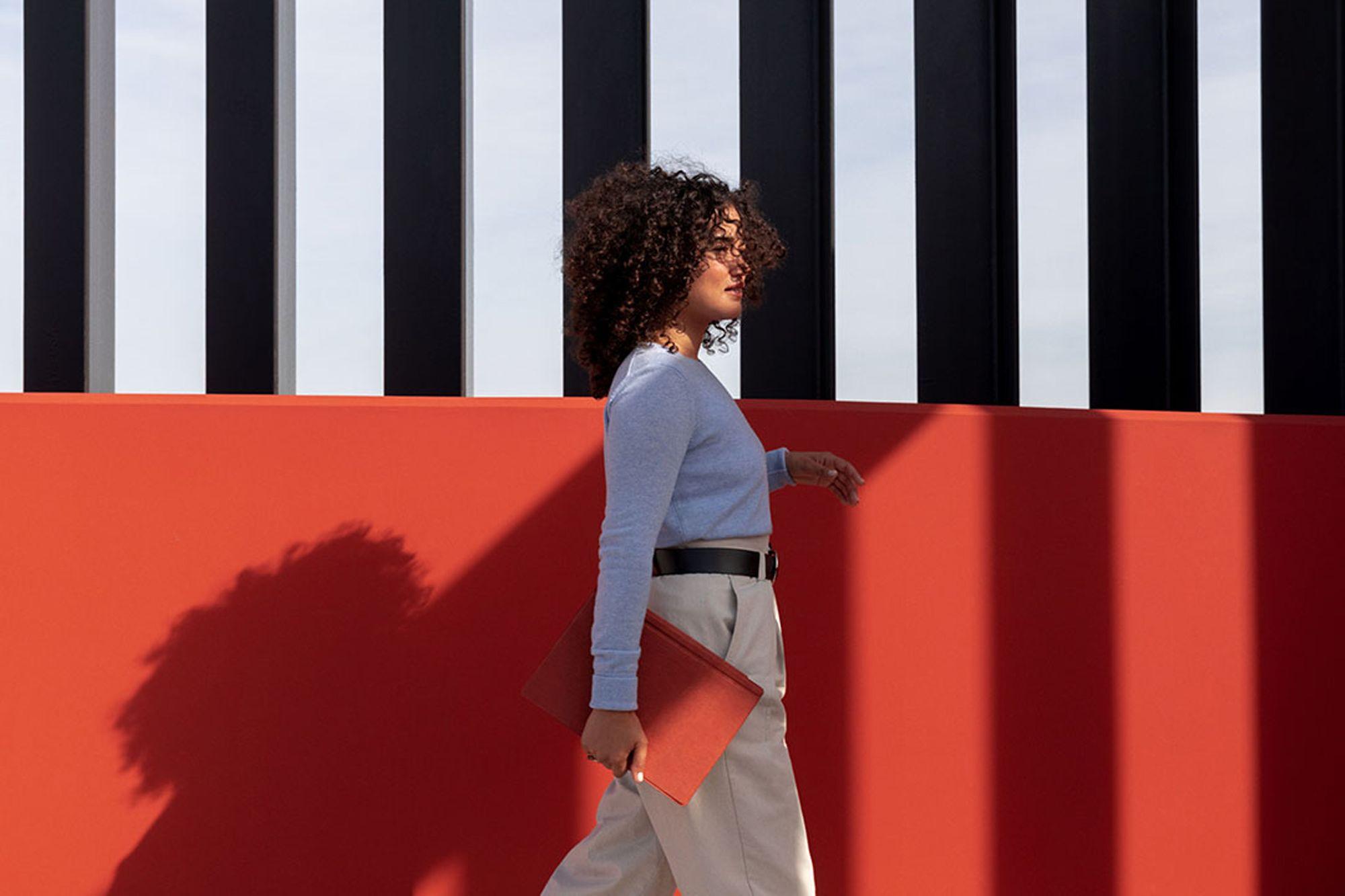 Eine Frau läuft mit dem Surface Pro 7 inklusive dem mohnroten Typecover in der Hand vor einer mohnroten Mauer entlang