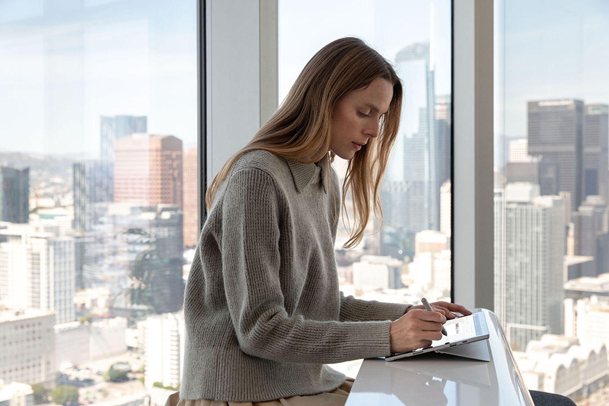 Eine Frau sitzt an einem Tisch vor einer Fensterwand, hinter der eine Großstadt zu sehen ist. Sie arbeitet mit dem Surface Pen auf dem Surface Pro 7