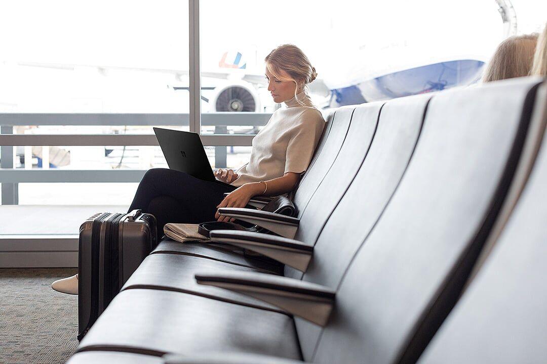 Eine Frau sitzt in der Wartehalle eines Flughafens und arbeitet mit ihrem Surface Laptop ortsunabhängig und flexibel