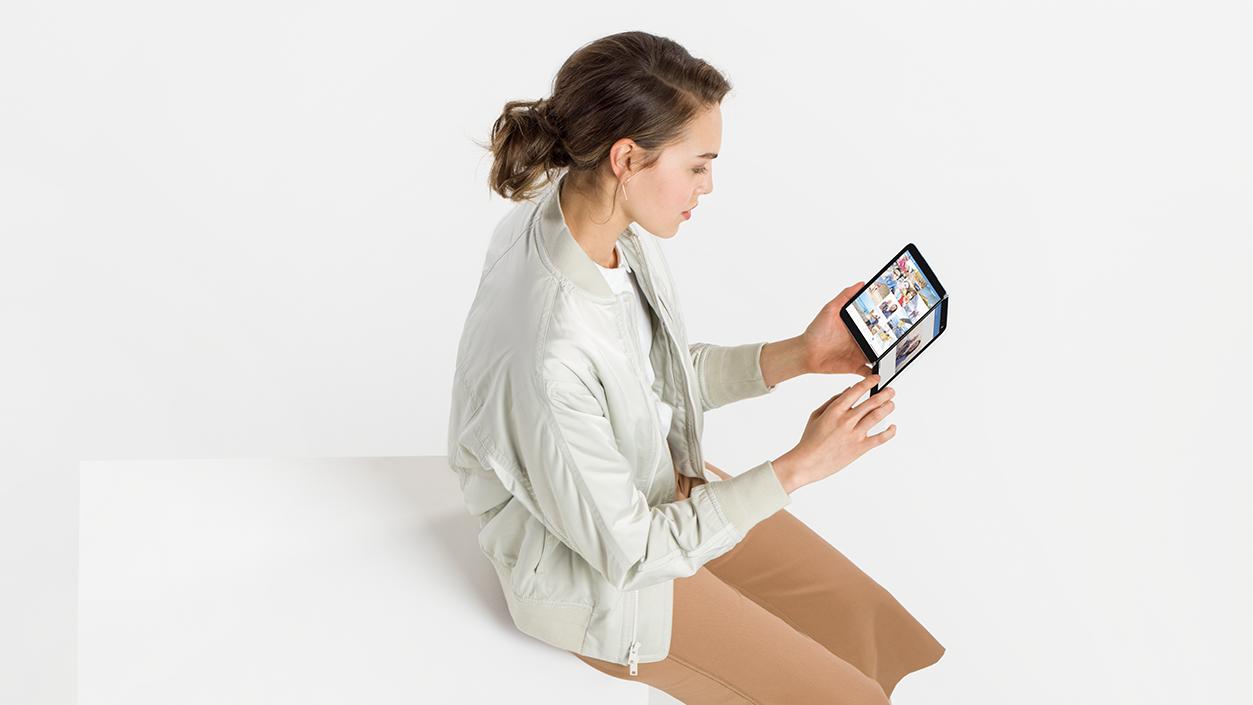 Eine Person sitzt auf einem Hocker und schaut auf das Surface Duo in ihren Händen.