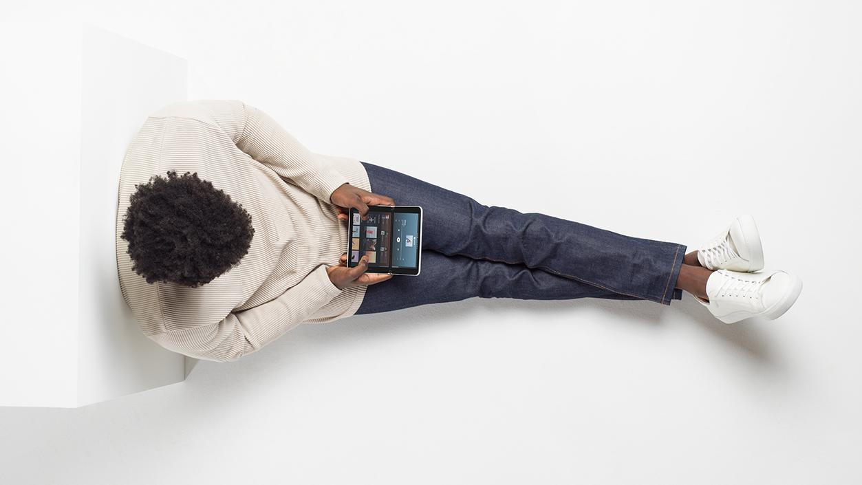 Vogelperspektive auf eine Person, die auf dem Boden sitzt und ein Surface Duo in den Händen hält.
