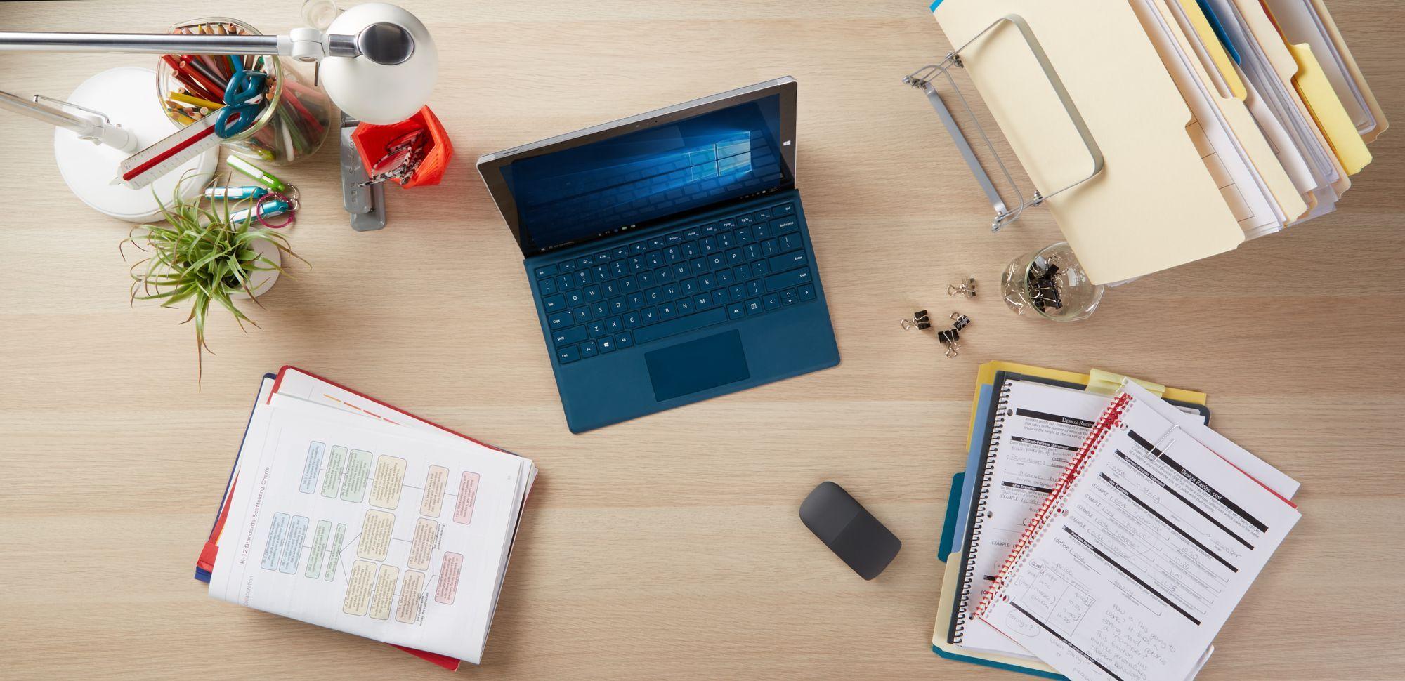 Ein Schreibtisch mit dem Surface Go zwischen verschiedenen Heftern, Akten und Schreibtischutensilien