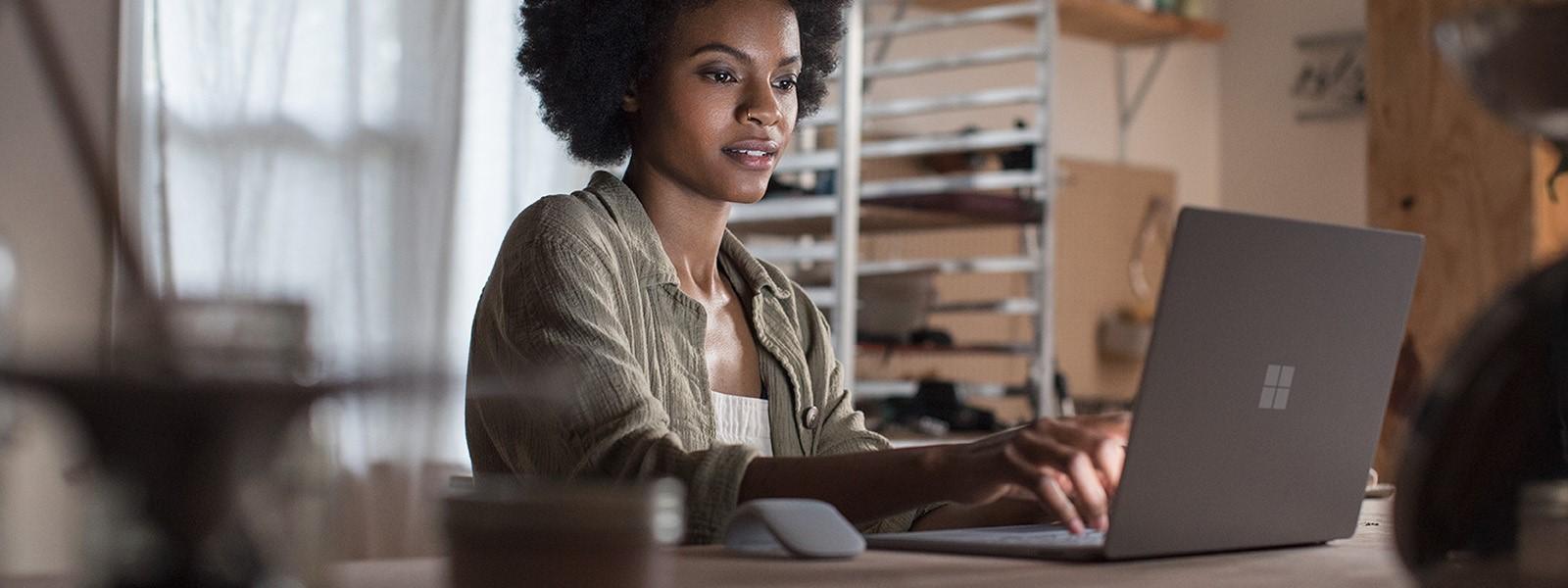 Eine Frau sitzt an einem Tisch und arbeitet mit einem Surface Laptop