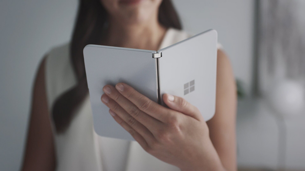 A person is holding a Surface Duo in one hand.
