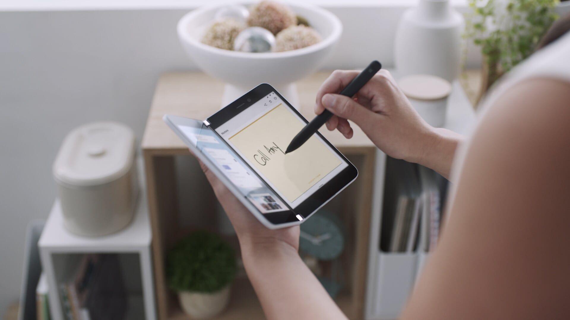 Eine Frau schreibt mit dem Surface Slim Pen auf dem Surface Duo