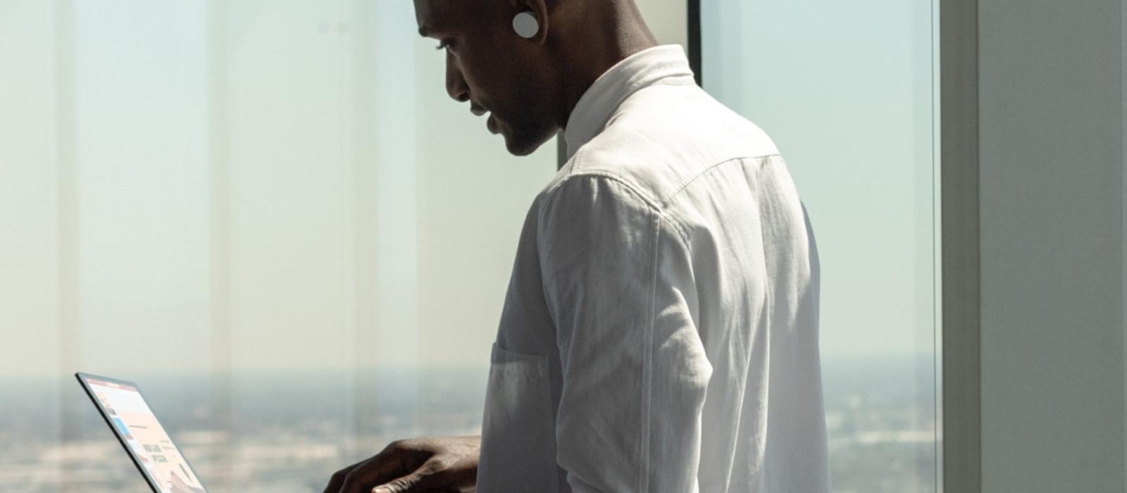 Die Seitenansicht eines Mann zeigt, wie er die Surface Earbuds im Ohr trägt und auf einen Surface Laptop schaut