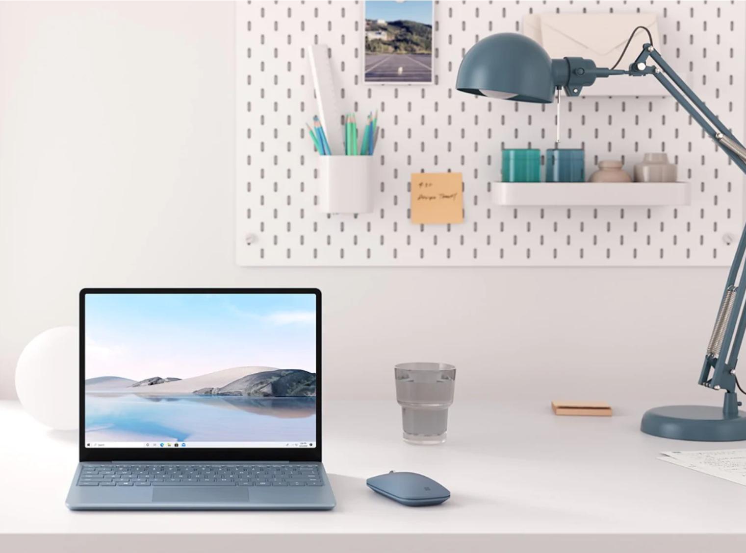Der Surface Laptop Go in Eisblau steht mit einer Surface Mobile Mouse in Eisblau in einer Schreibtisch-Szenerie.