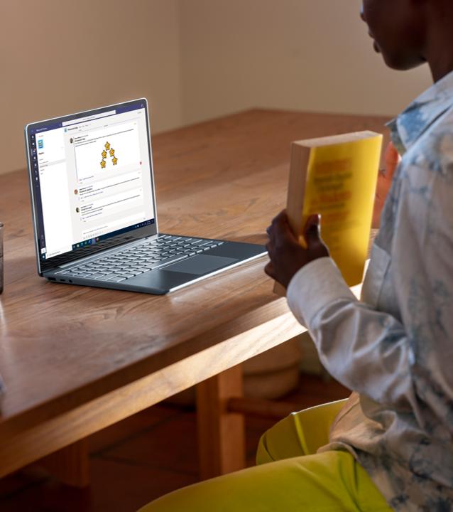 Ein Kind sitzt an einem Schreibtisch mit einem Buch in den Händen, vor ihm ist der Surface Laptop Go in Eisblau auf dem Schreibtisch platziert.