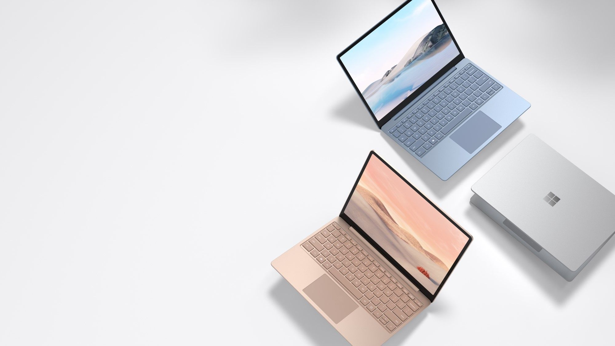 Die Surface Laptop Go Devices in Eisblau, Sandstein und Platin sind nebeneinander in verschiedenen Modi auf einem grauen Untergrund platziert.