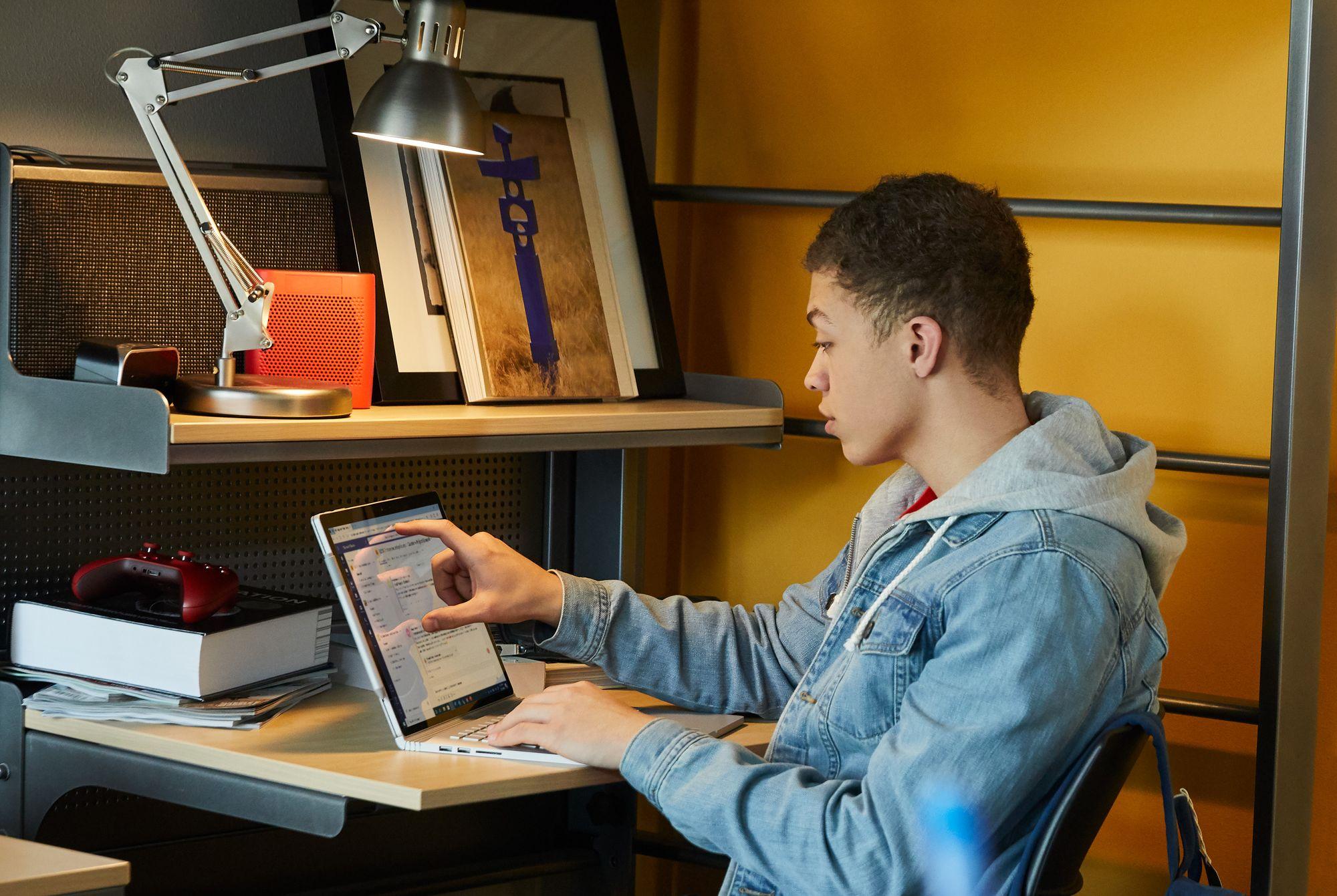 Eine Person sitzt an einem Schreibtisch und arbeitet an einem Surface Book.