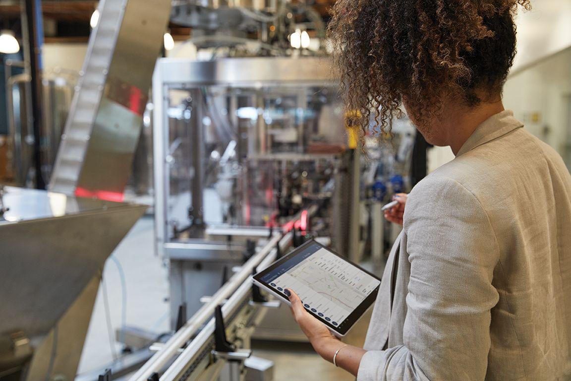 Eine Person steht in einer Produktionshalle und arbeitet an einem Surface Pro