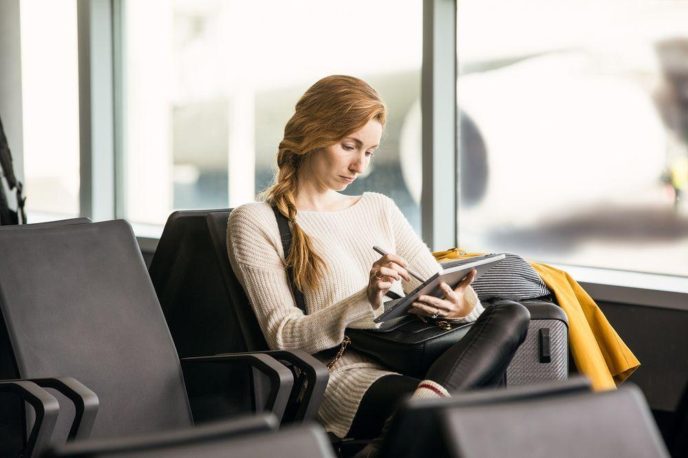 Eine Frau sitzt an einem Gate am Flughafen und arbeitet an einem Surface Pro