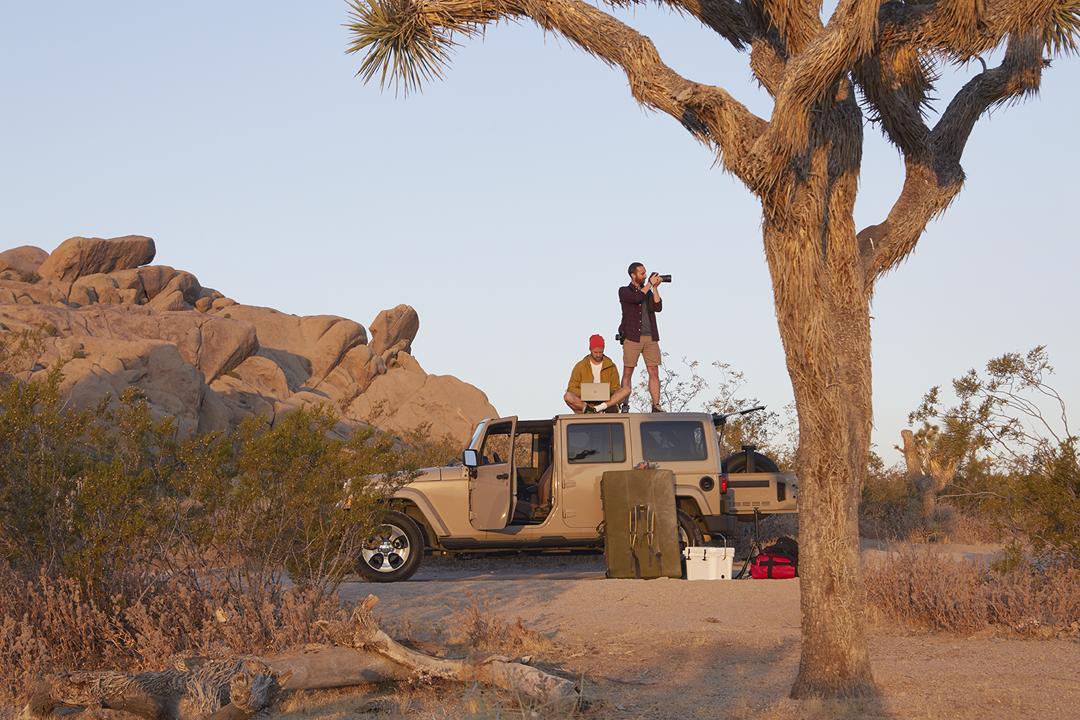 Zwei Männer befinden sich auf dem Dach eines Jeeps. Einer von ihnen fotografiert, der andere arbeitet an einem Surface Book.