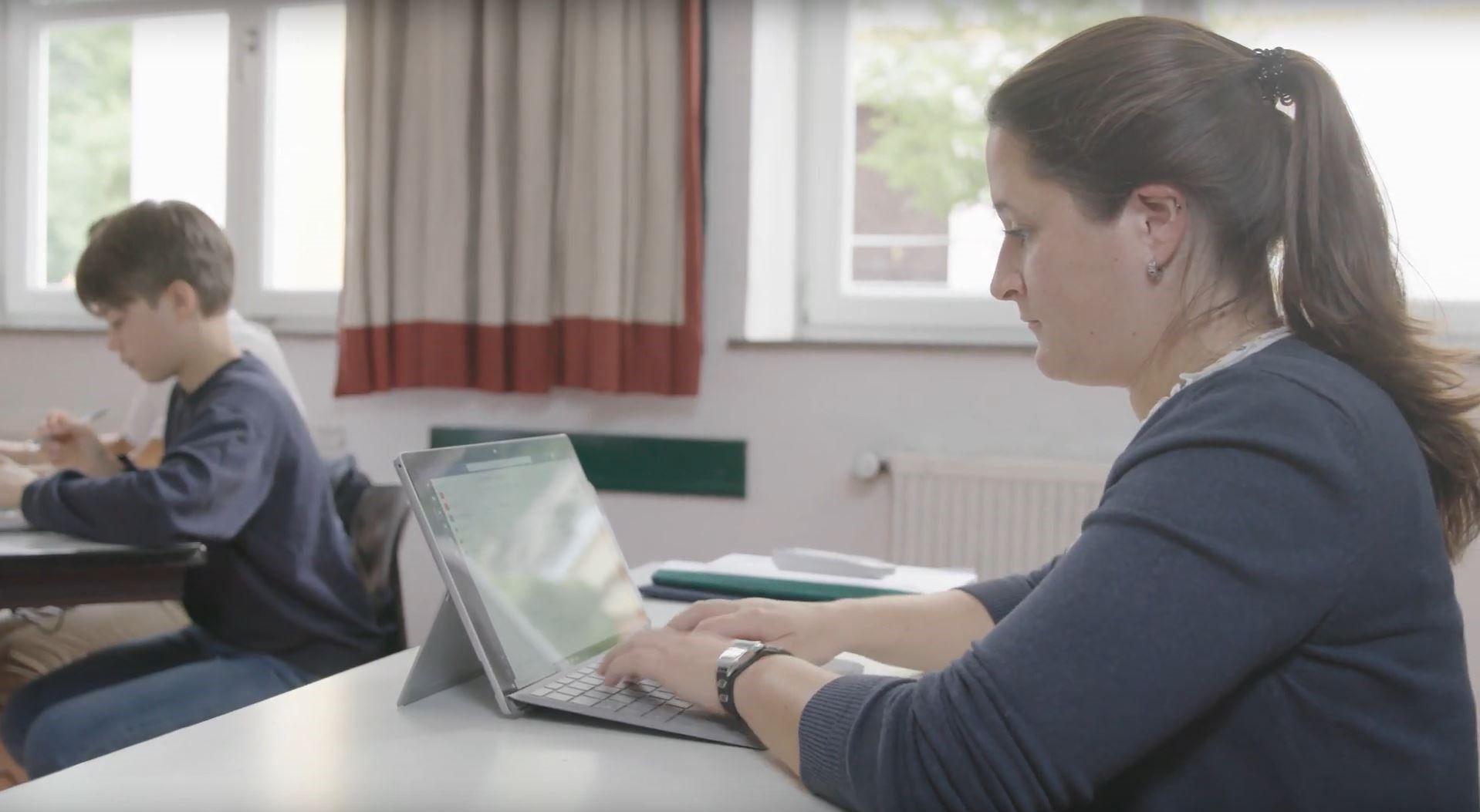 In einem Klassenzimmer schreibt eine Lehrerin etwas in Microsoft Teams auf dem Surface Pro
