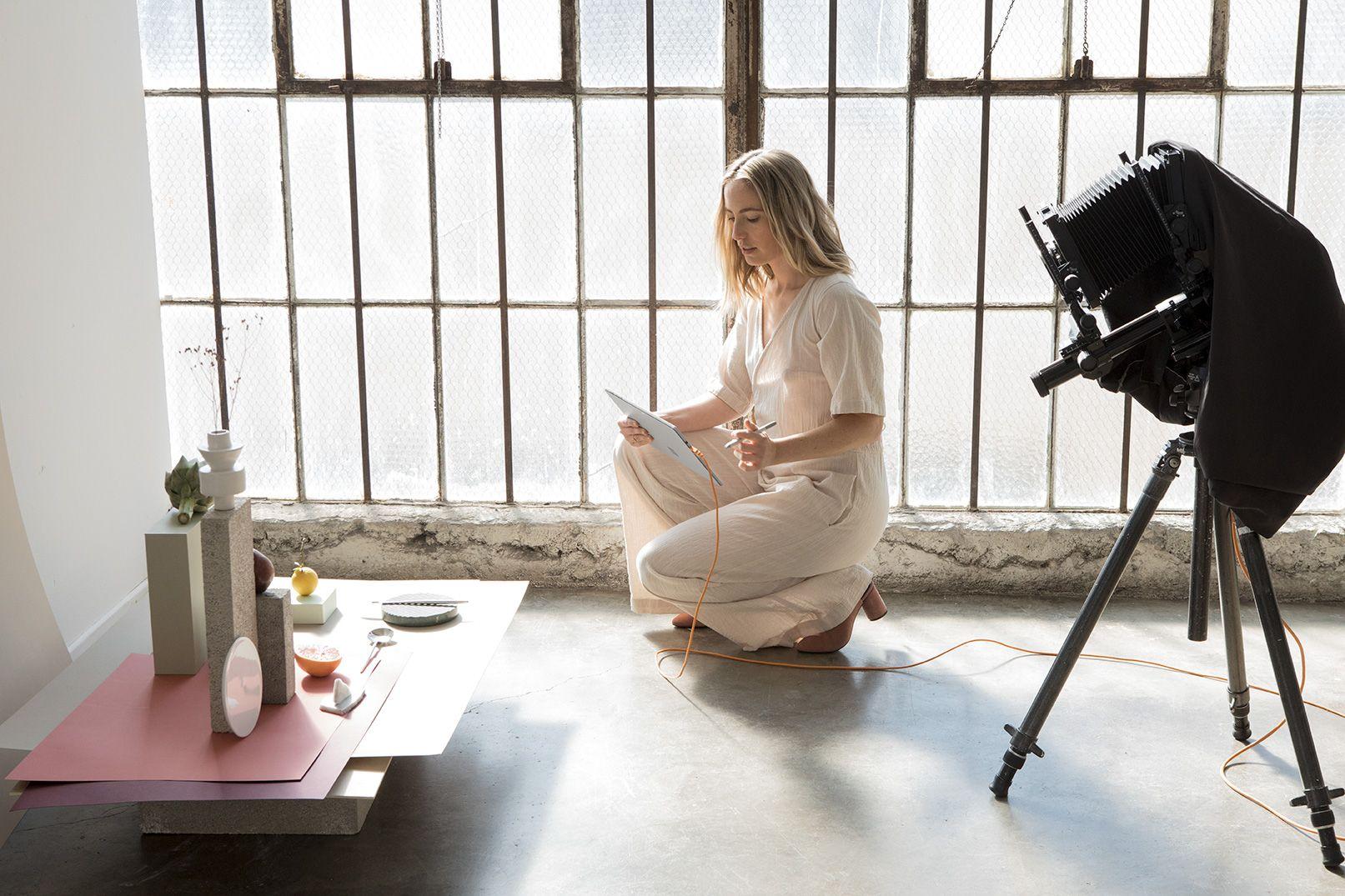Eine Frau arbeitet in einem Fotostudio an einem Surface Pro.