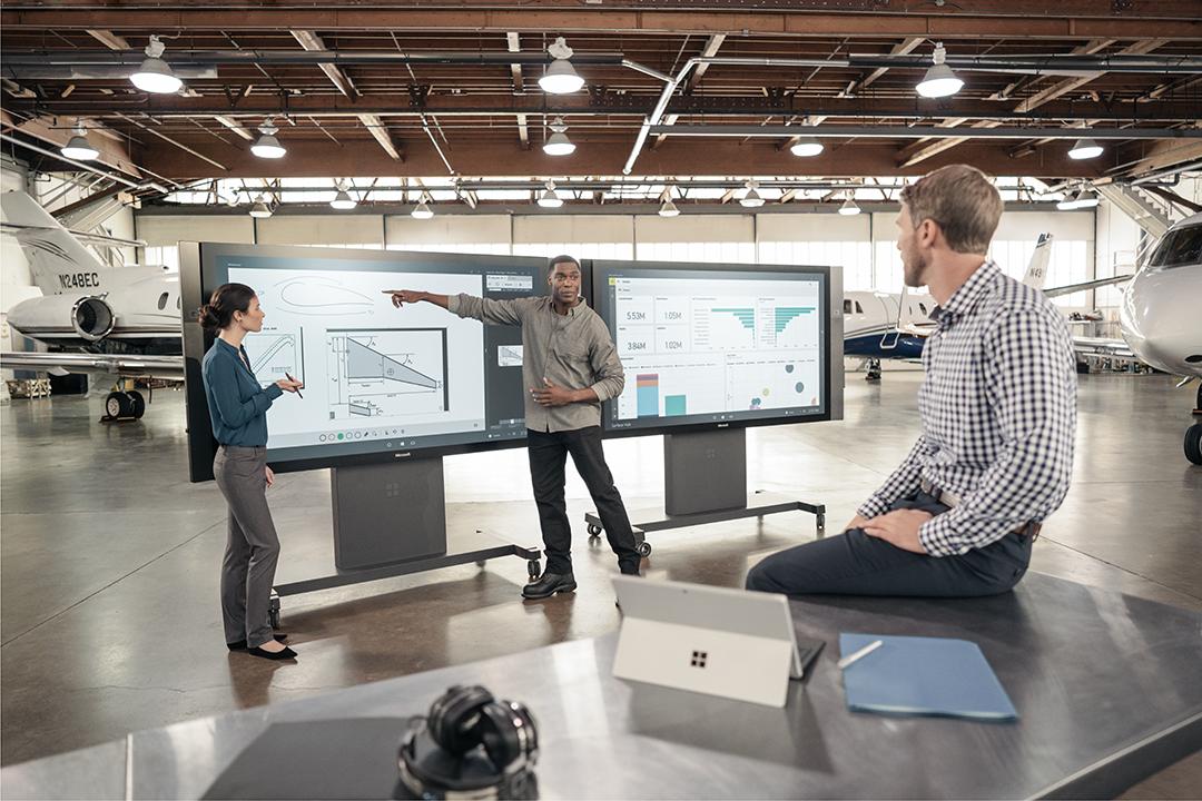 Zwei Personen stehen vor zwei Surface Hubs. Ein Mann sitzt vor ihnen auf einem Tisch. Neben ihm steht ein Surface Pro.
