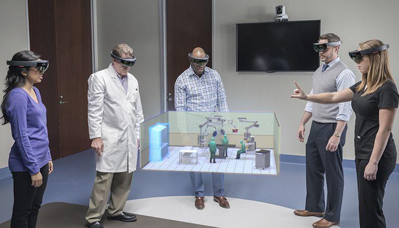 Fünf Personen tragen eine HoloLens. In der Mitte der Personen ist ein Hologramm.