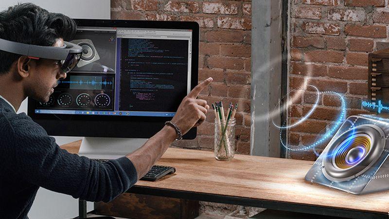 Ein Mann trägt eine HoloLens und interagiert mit einem Hologramm.