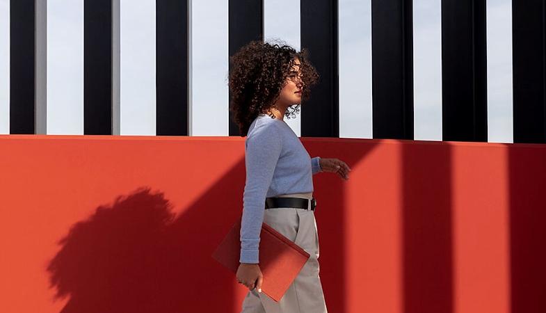 Eine Frau lauft mit einem Surface Pro vor einem Gebäude entlang.