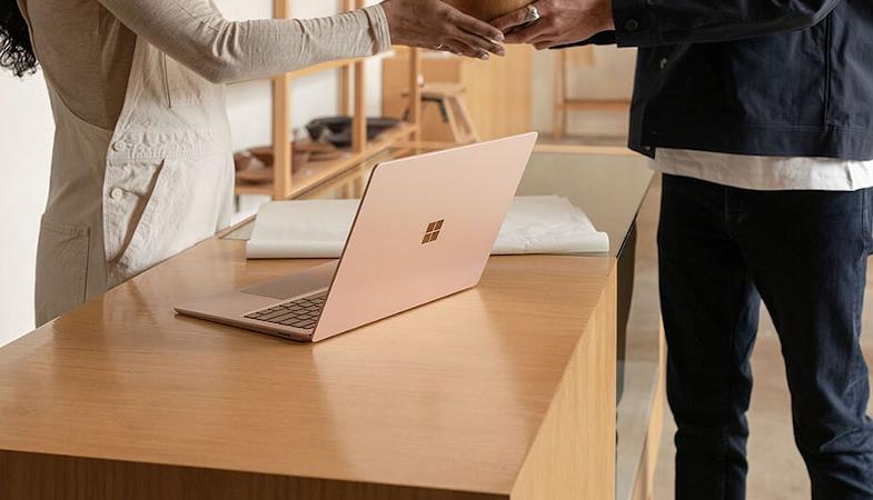 Eine Frau übergibt einem Mann einen Gegenstand über einen Tisch, auf dem ein Surface Laptop in Sandstein steht