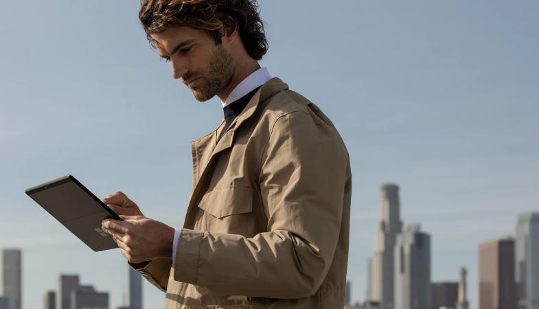 Ein Mann steht vor einer Stadtkulisse und tippt auf das Surface Pro X