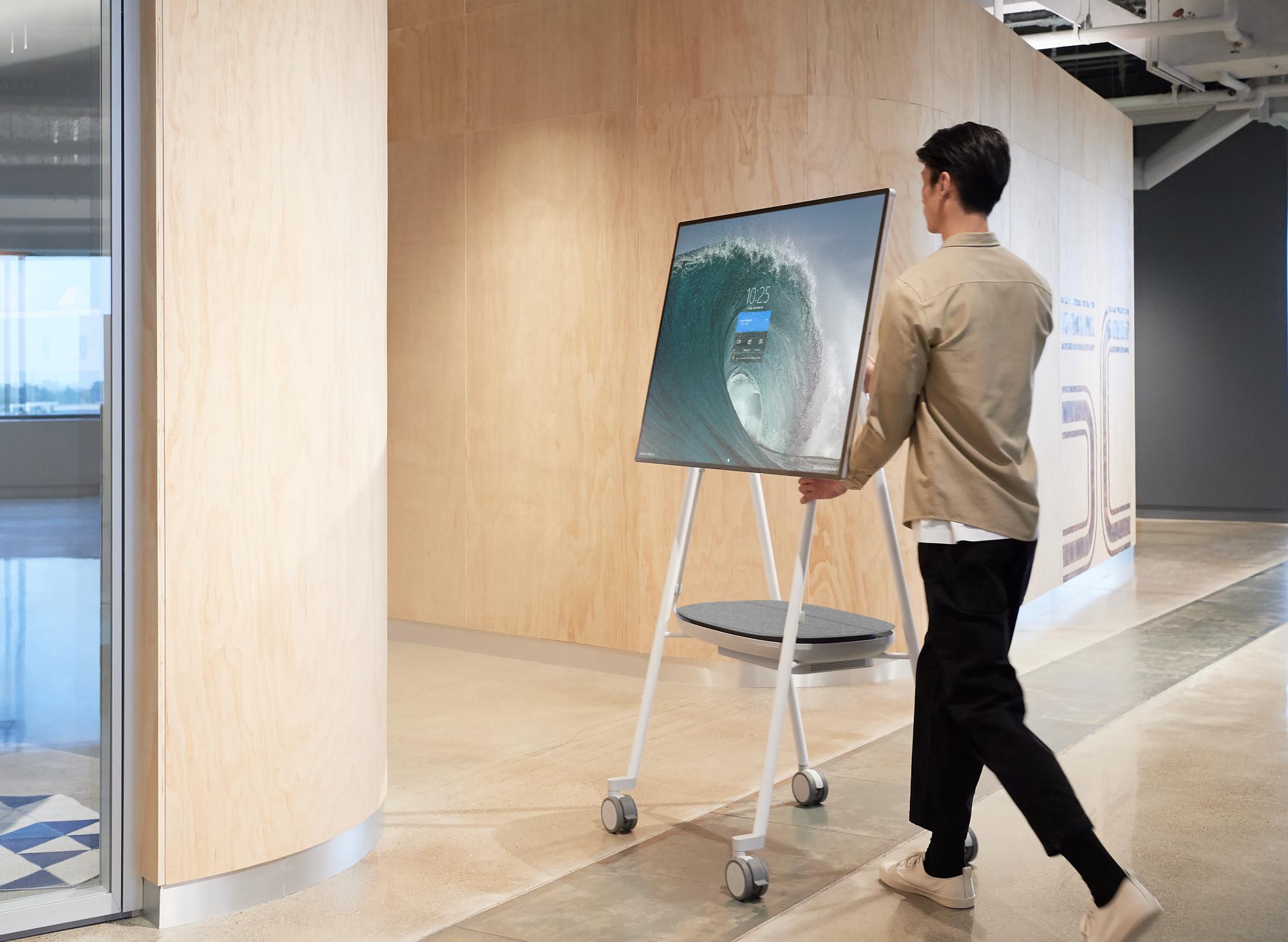 Ein Mann schiebt das Surface Hub 2 über den Flur eines Büros
