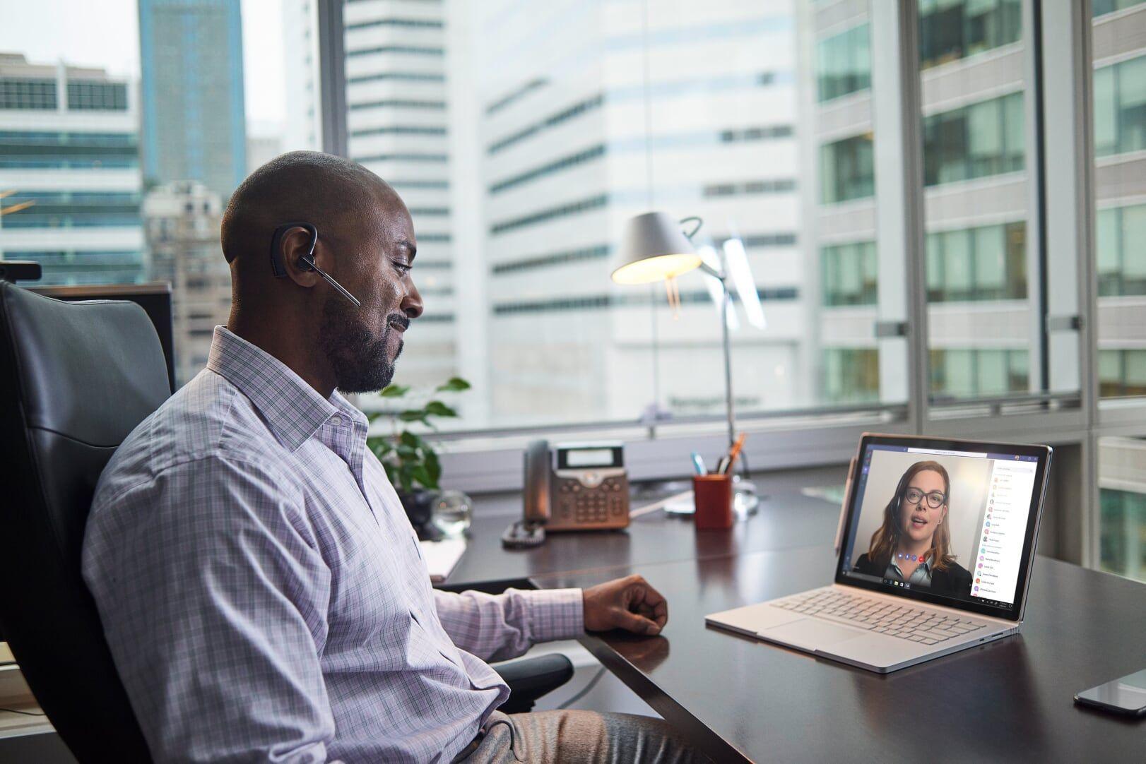 Ein Mann sitzt am Schreibtisch und telefoniert per Microsoft Teams Video auf seinem Surface Book mit einer Frau