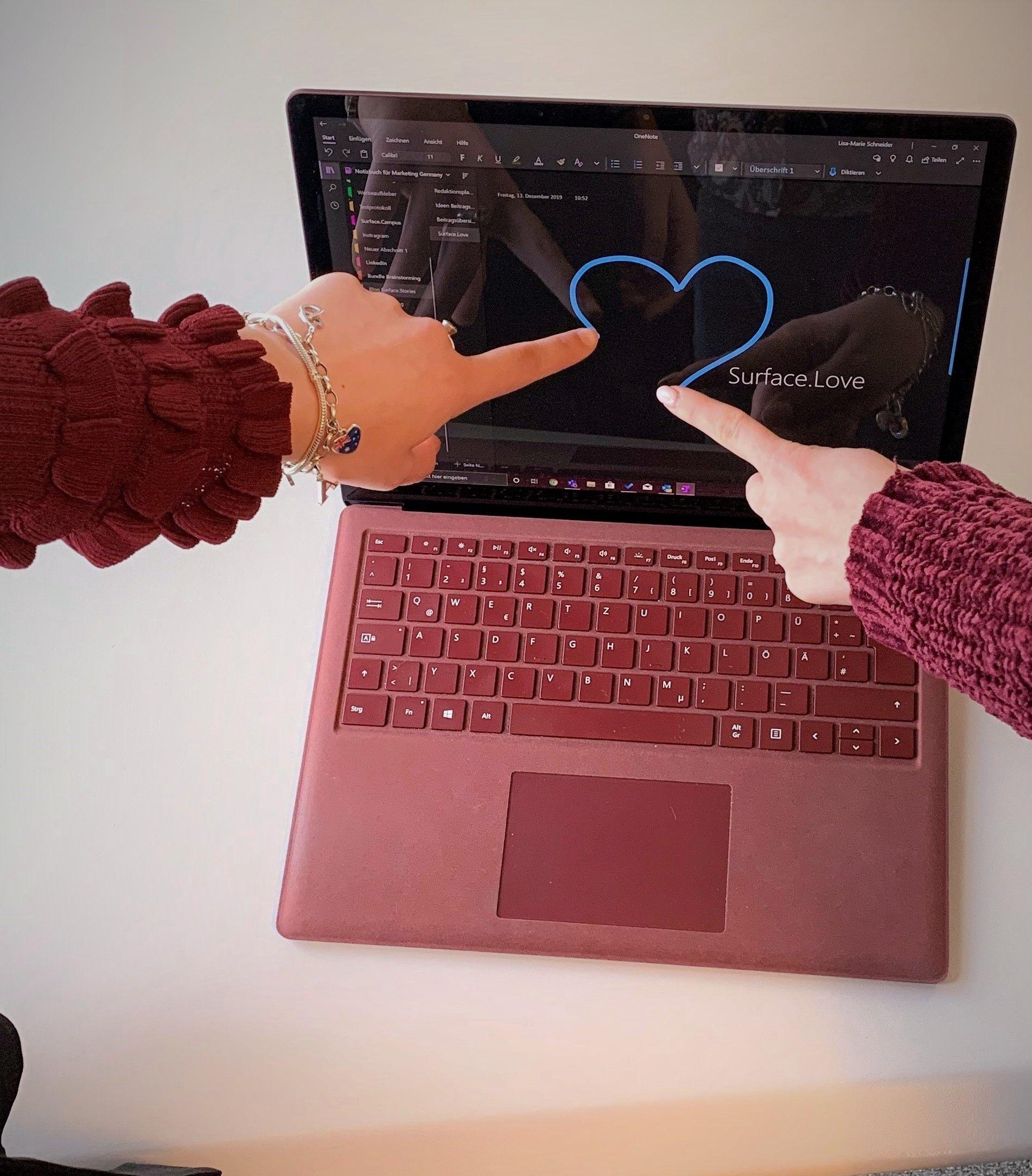 Zwei Personen malen mit ihrem Zeigefinger das blaue Herz-Logo von Surface.Love in OneNote auf dem Surface Laptop in Bordeauxrot