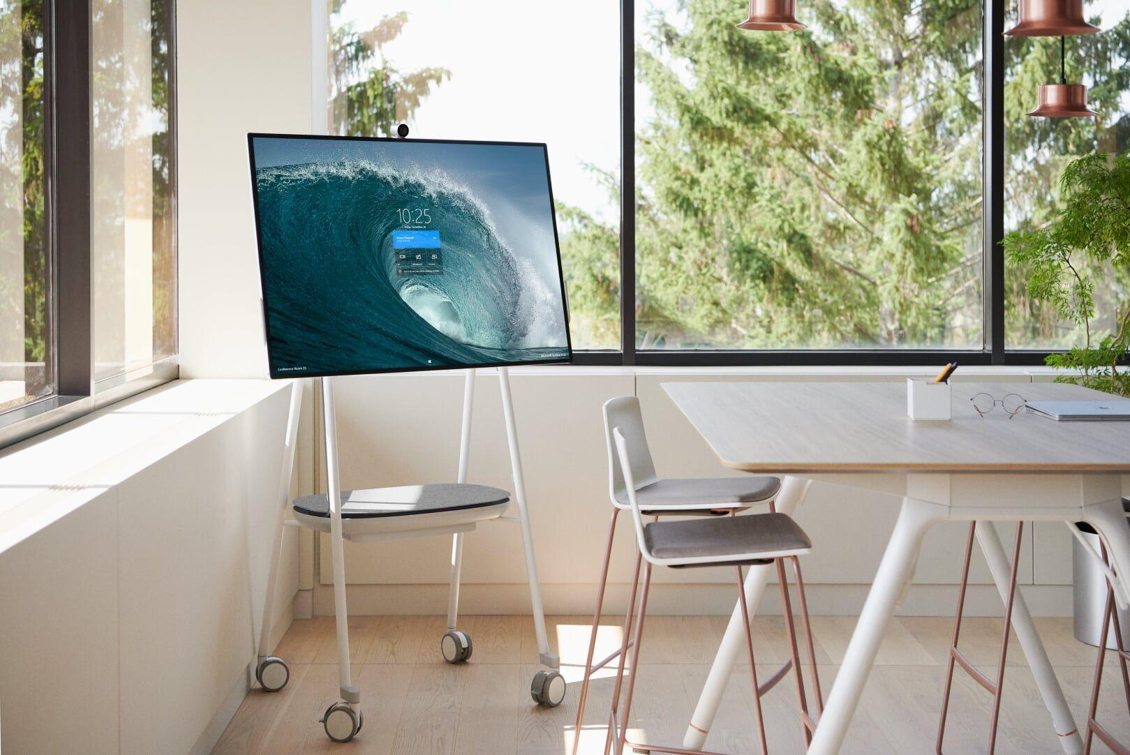 Ein Surface Hub 2 steht in eine Büroraum hinter einem Tisch mit mehreren Stühlen