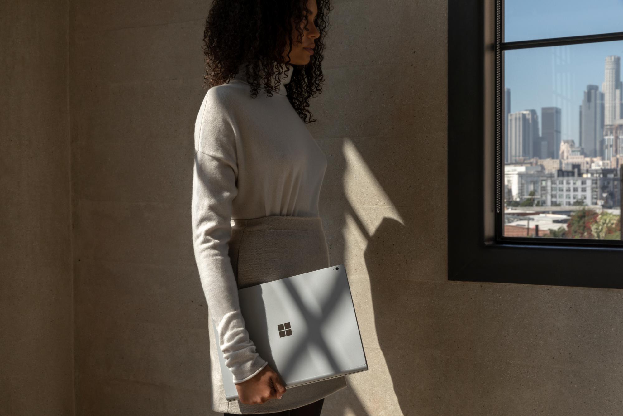 Eine Frau steht in einem Raum vor einer beigefarbenen Wand mit dem Surface Book 3 in der Hand
