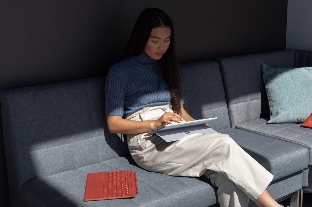 Eine Frau sitzt auf einer Couch und arbeitet mit dem Surface Pen auf dem Bildschirm des Surface 7 in Platin