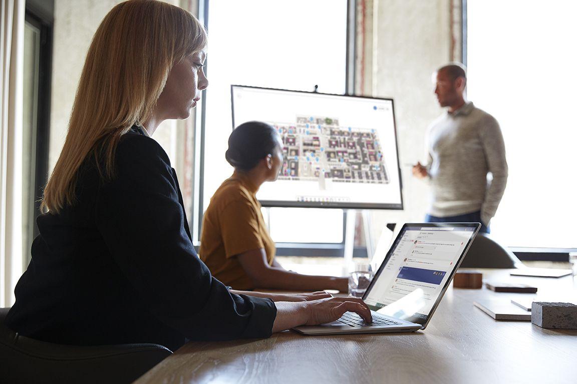 In einem Meetingraum arbeiten drei Personen gemeinsam mit dem Surface Hub und Surface Laptops