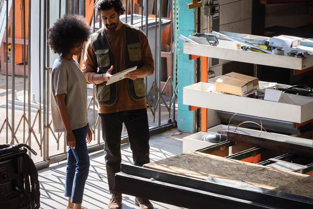 In einer Werkstatt zeigt ein Mann einer Frau etwas auf dem Surface Go