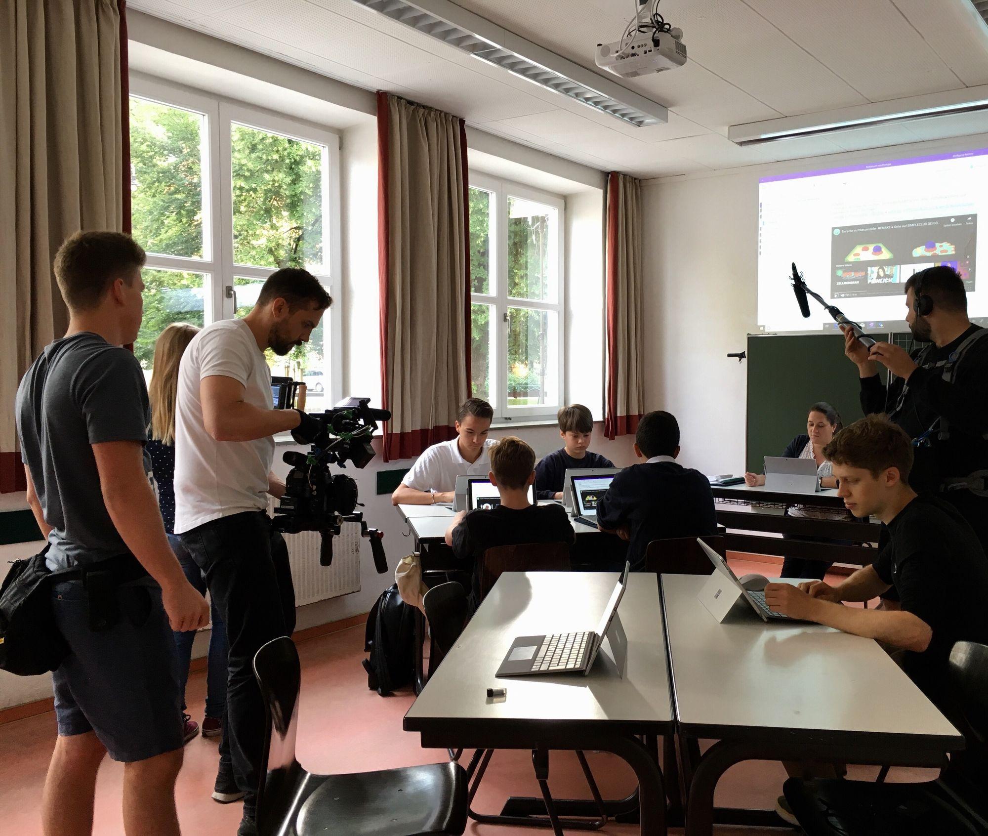 Ein Filmteam dreht eine Szene im Klassenraum, in der Lernenden an ihren Surface Geräten arbeiten