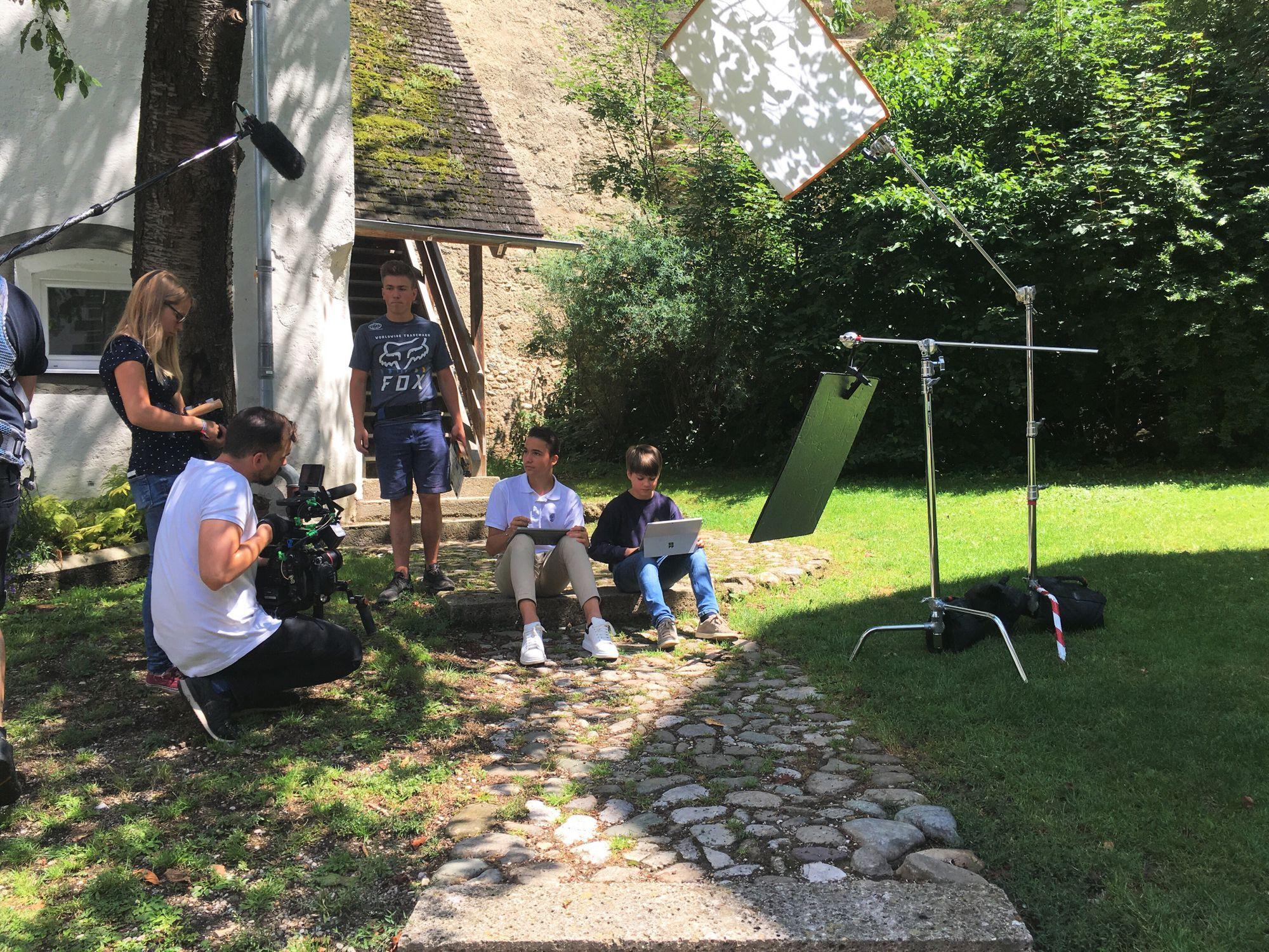Eine Szene wird vom Filmteam abgedreht, in der Lernende auf einer Wiese des Schulgeländes sitzen
