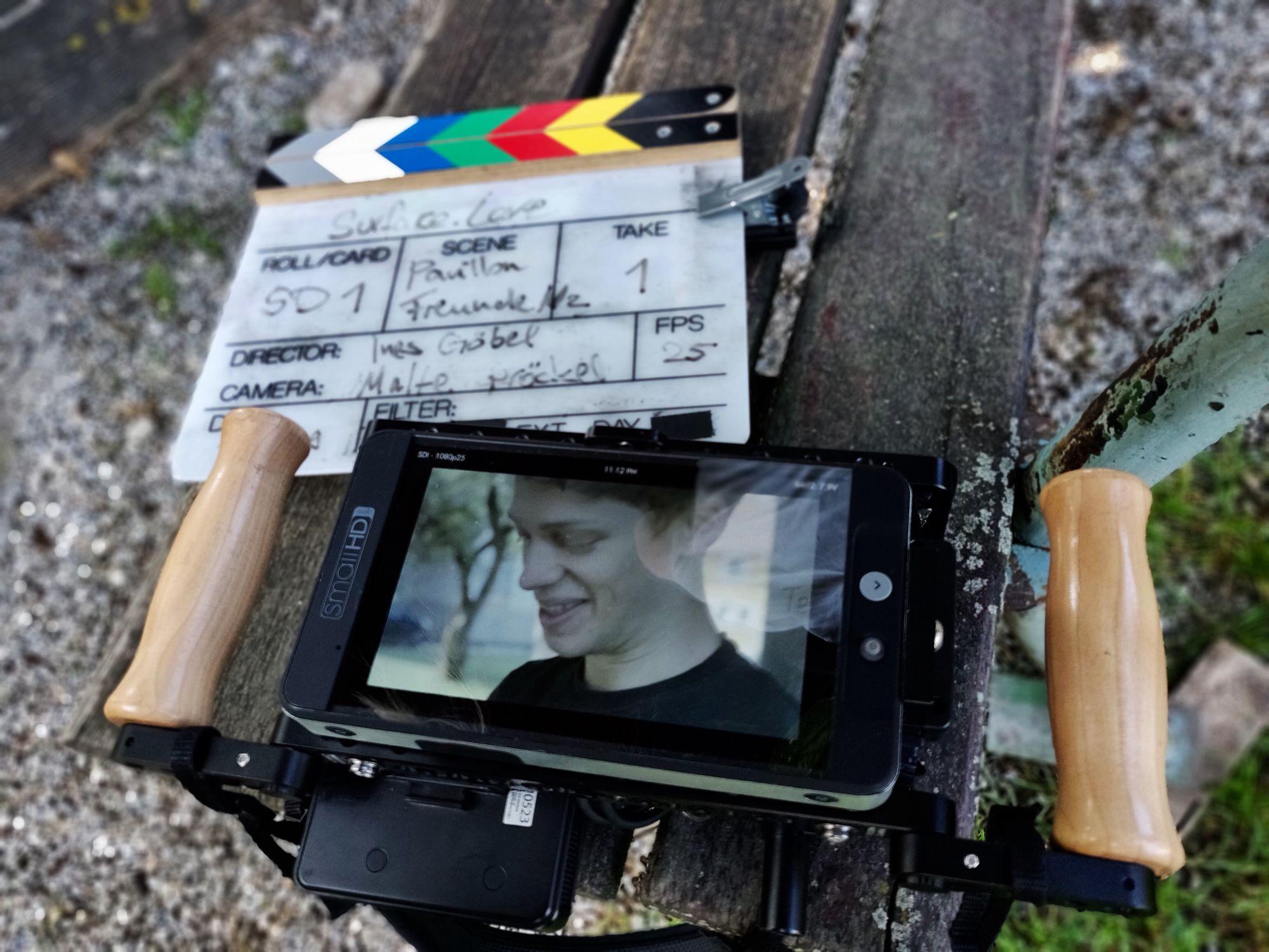 Eine Filmklappe und ein Ausspielmonitor, auf dem eine gedrehte Szene angezeigt wird, liegen auf einer Bank
