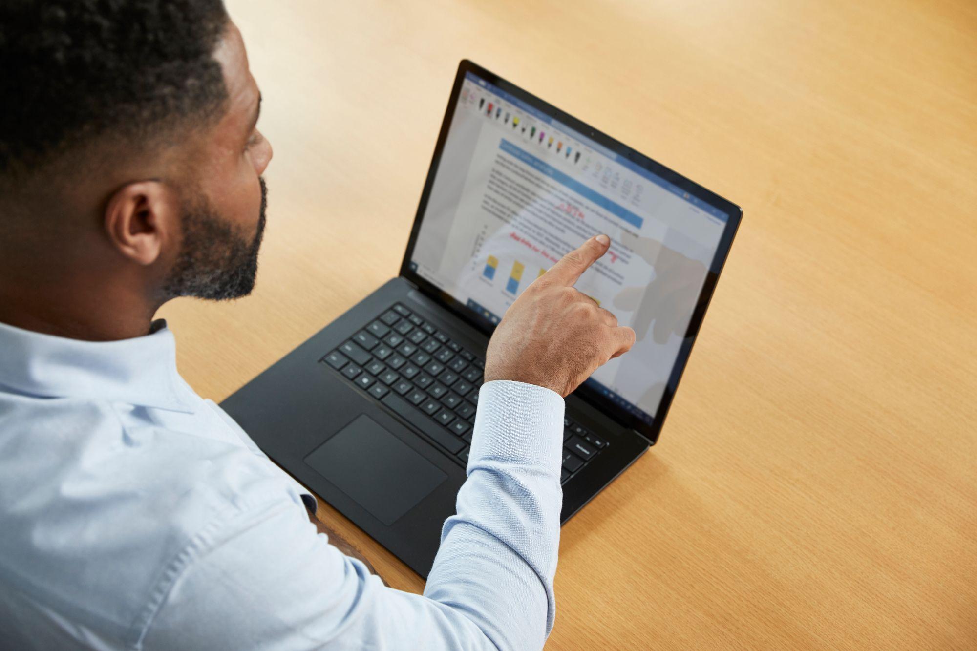 Ein Mann korrigiert per Touch-Funktion auf dem Bildschirm des Surface Laptops einen Text in Word