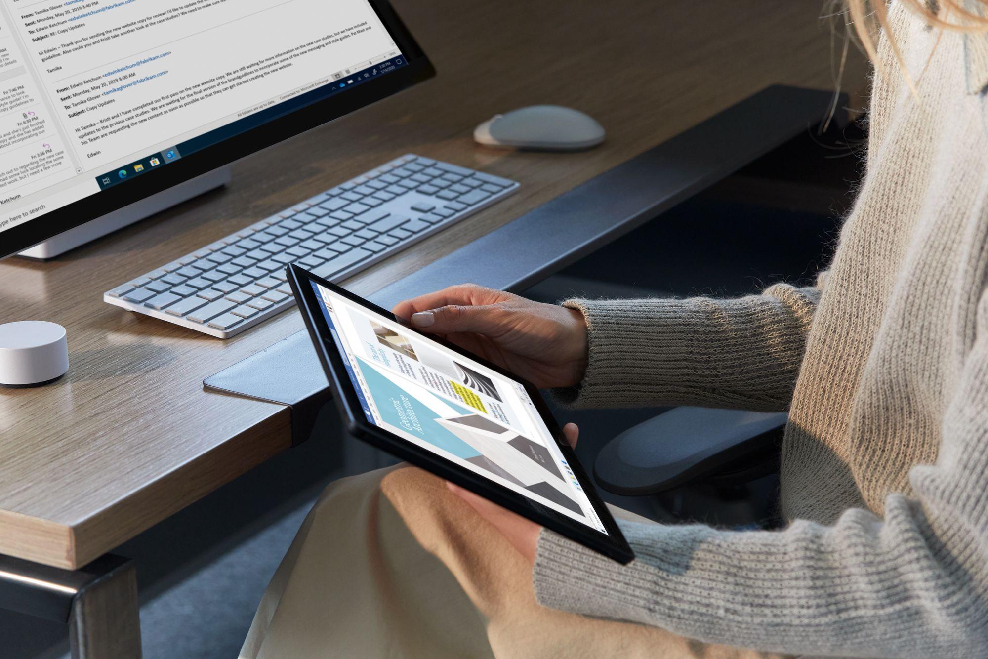 Eine Frau sitzt an einem Schreibtisch und hält ein Surface Pro in der Hand, auf dem Schreibtisch ist ein Surface Studio inklusive Zubehör platziert