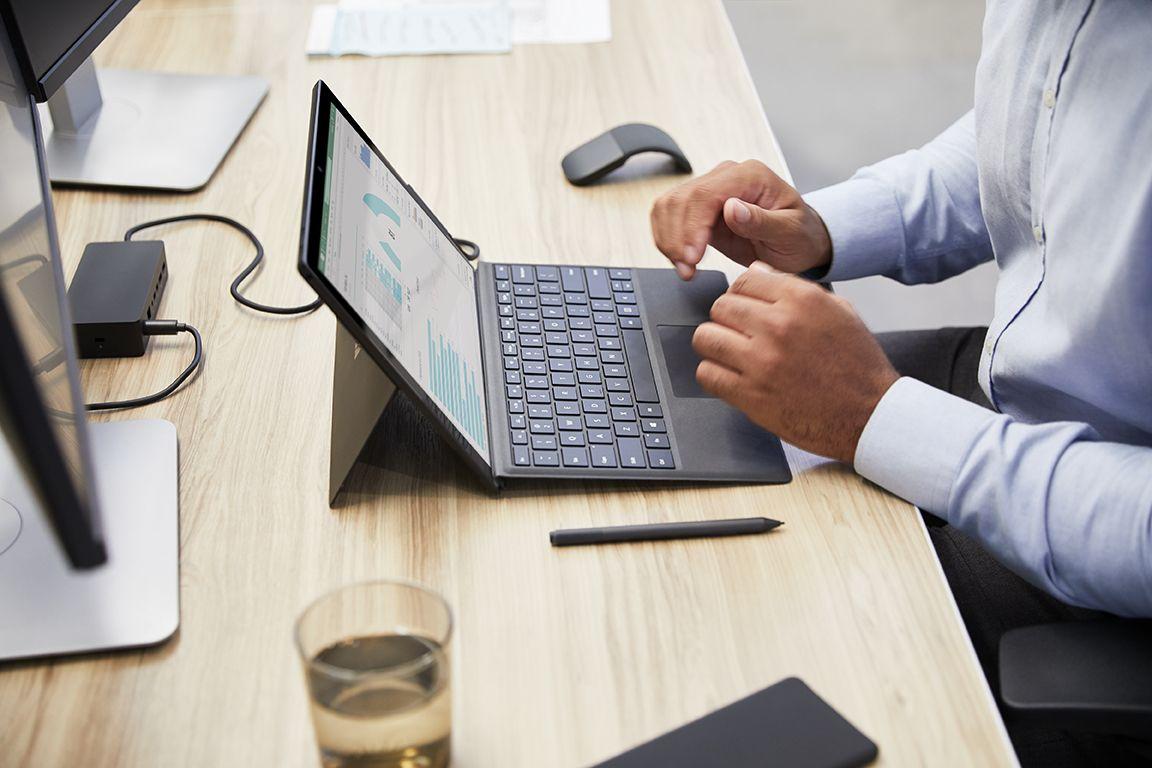 Ein Mann sitzt an einem Schreibtisch und arbeitet auf dem Surface Pro