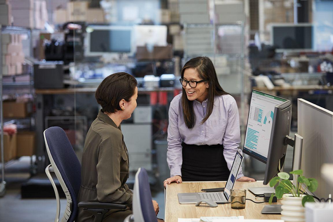 Zwei Frauen unterhalten sich in einer Büro-Szenerie an einem Schreibtisch miteinander