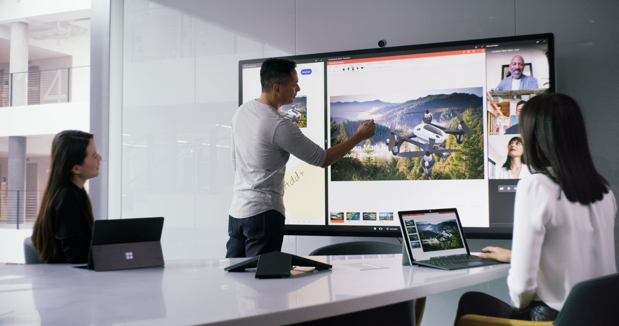 In a meeting room, two women are sitting at a conference table with their Surface devices and a man is standing at the Surface Hub, working on a presentation with the Surface Hub 2 Pen