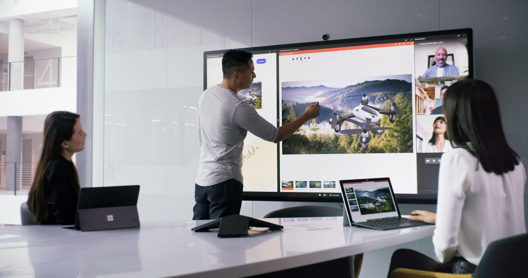 In einem Meetingraum sitzen zwei Frauen mit ihren Surface Geräten an einem Konferenztisch, ein Mann steht am Surface Hub und stellt eine Präsentation vor