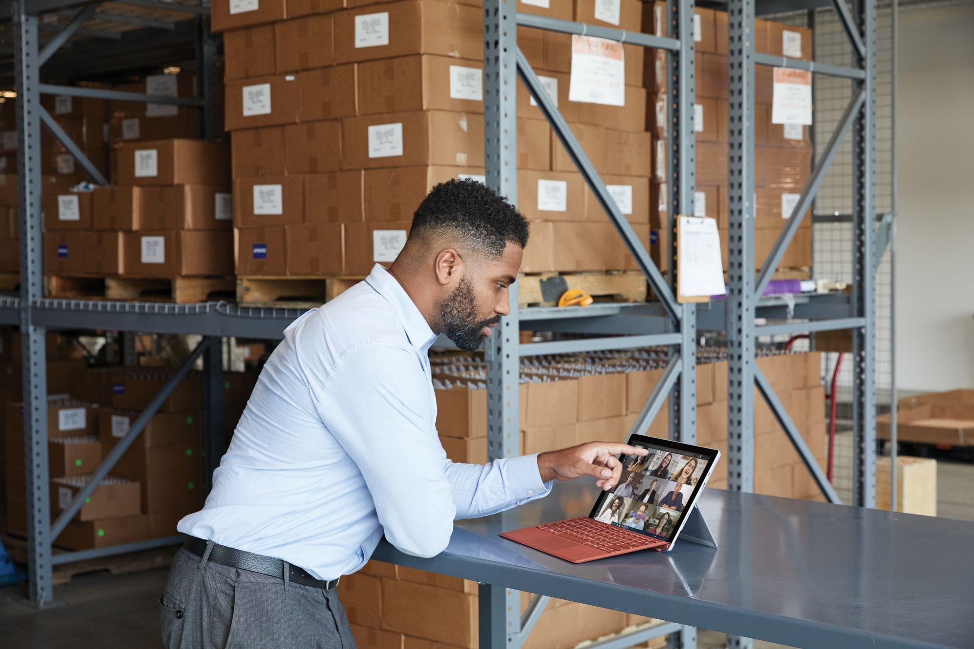 In einem Warenlager steht ein Mann an einem Tisch und schaut auf das Surface Pro 7 Plus im Laptop-Modus, auf dem eine Videokonferenz zu sehen ist