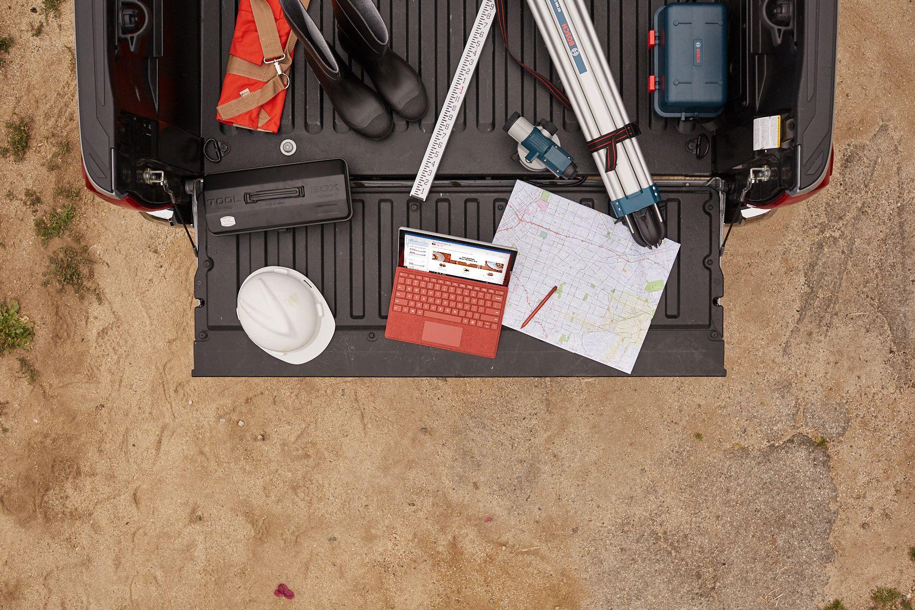 Im Kofferraum eines Pick-ups steht das Surface Pro 7+ inmitten von Werkzeugen