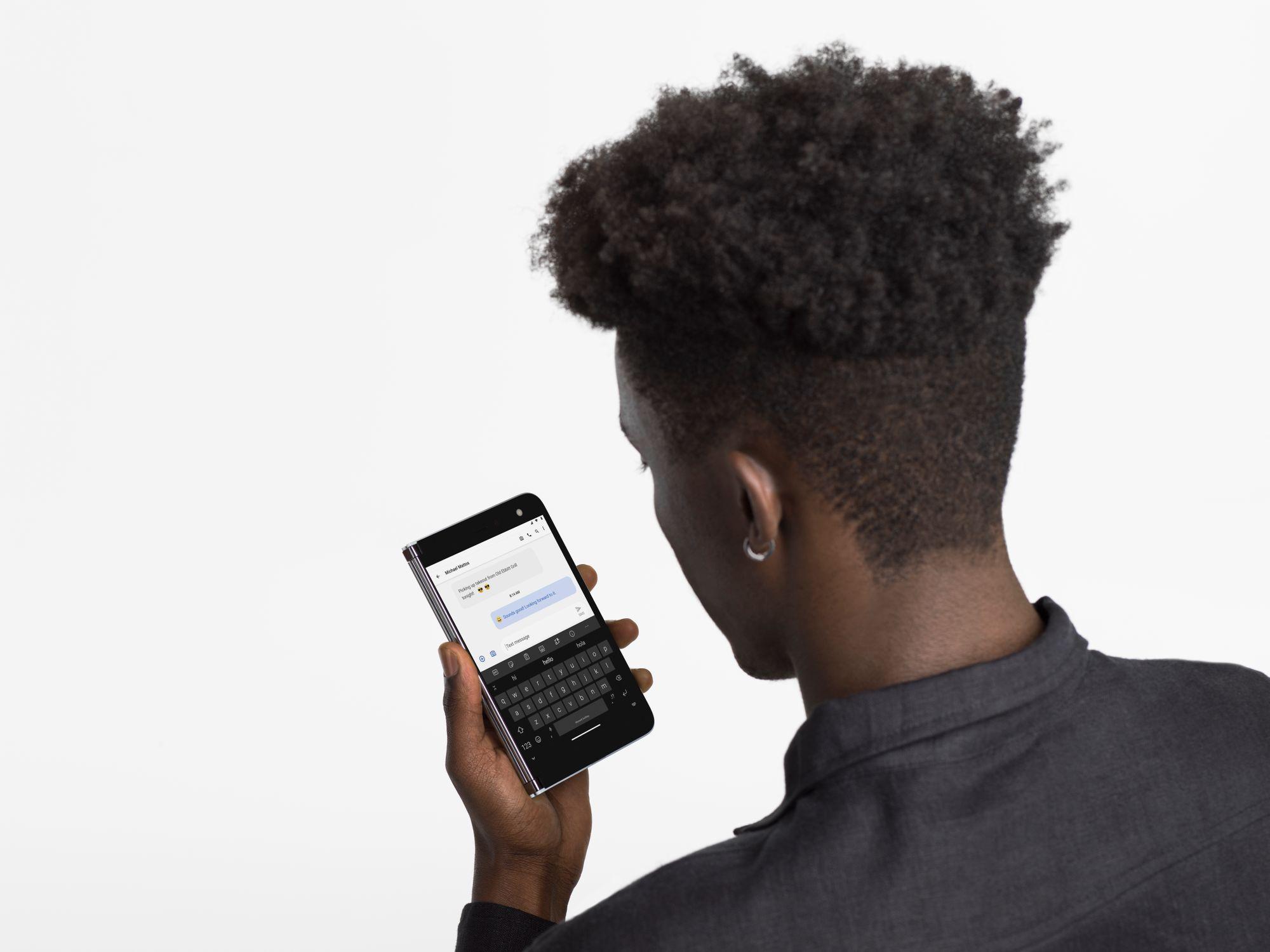 Ein Mann hält das Surface Duo im Telefon-Modus in der Hand und schaut auf einen Bildschirm, auf dem ein Nachrichtenchat geöffnet ist